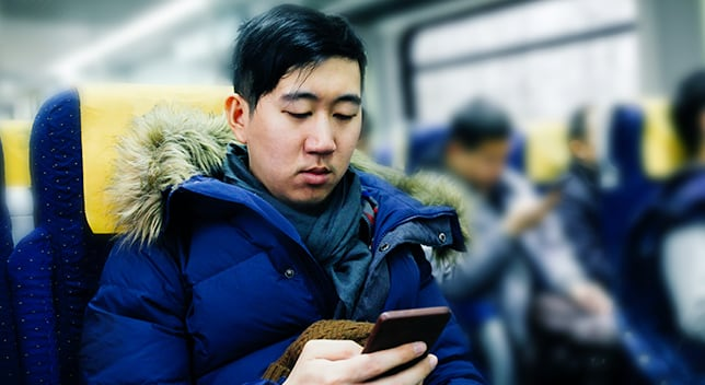 A man in a winter jacket sits in a seat on a public train and looks at his phone