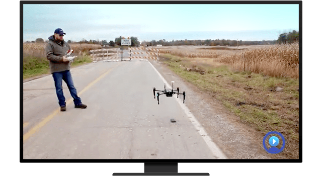 A person operating a drone outside in the middle of an empty road
