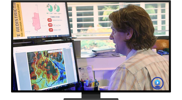 A person looking at two desktop monitors that have a dashboard and digital map displayed