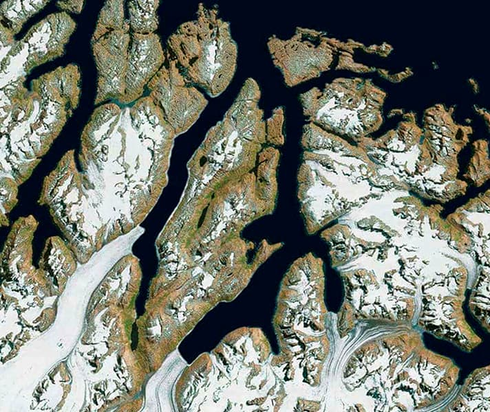 Satellite image of snow-covered land meeting water inlets