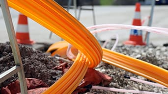 Orange wires running into the ground of a construction site