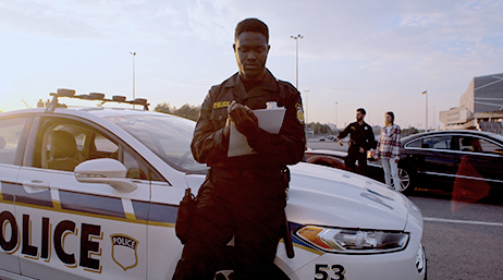 Image of a law enforcement officer with his vehicle