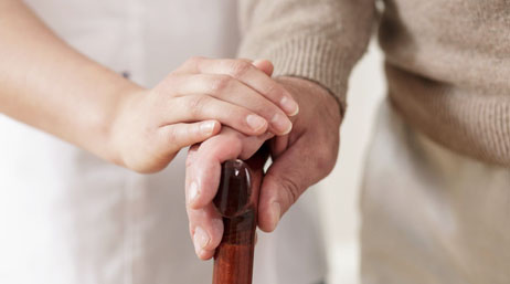 Care worker with a hand on their patient's hand on a cane