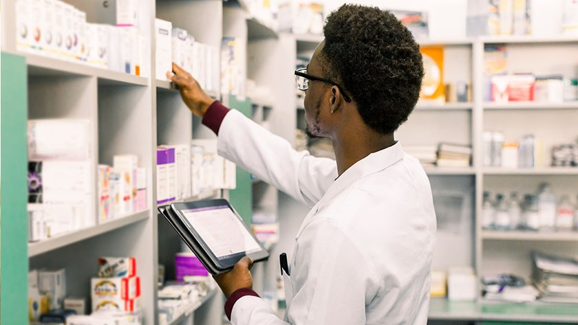 Pharmacist checking medication stocks while consulting a tablet