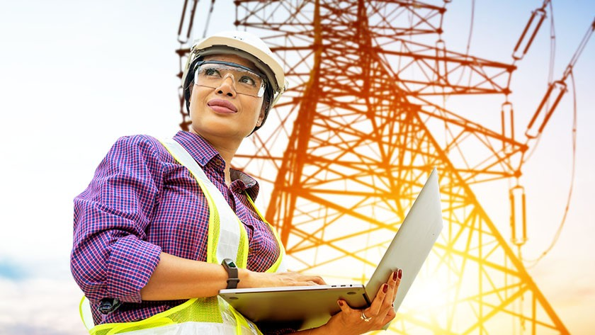 Woman worker checking information on a laptop while checking a large electrical tower