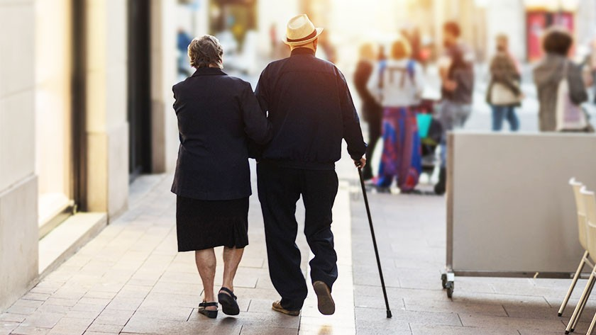 Older couple walking together on a city sidewalk