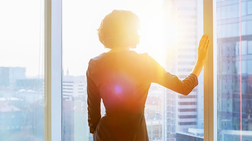 Businesswoman looking out of a high office building window