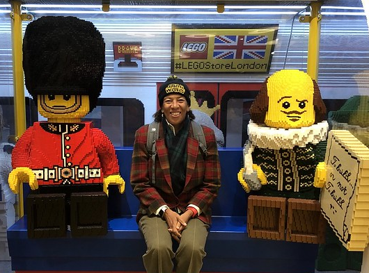 Dawn Wight sits in between two life-size sculptures made of LEGOS. The Sculpture on the right is a royal British guard and the sculpture on the left is Shaekspeare.