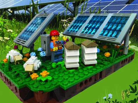 LEGO solar farm complete with LEGO green grass, LEGO Blue solar panels, and a LEGO solar farm worker wearing a red hat