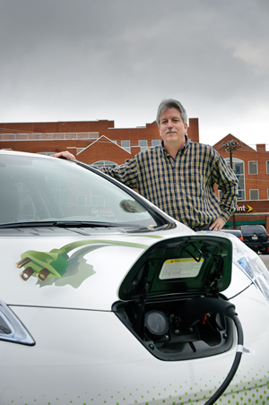 Brown charges one of the NES electric vehicles.