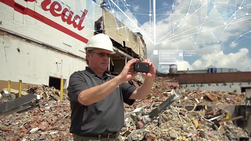Man using GIS mapping software on smartphone at an earthquake disaster location