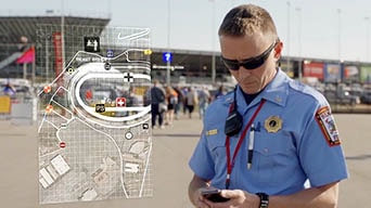 Firefighter looks at map on smartphone at NASCAR event