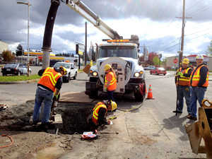 A Pierce County Public Works Road Operations crew multitasks as they perform a targeted annual storm drainage structure cleaning.