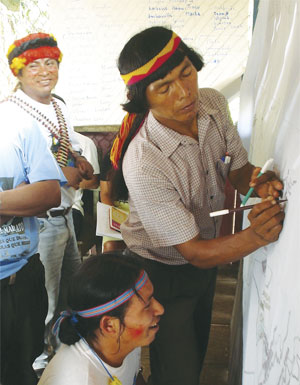 Leaders of the Achuar use maps to draw their land. (Photo courtesy of AmazonGISnet.)