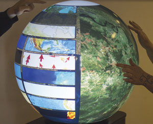A pair of analysts works with ArcGIS on the PufferSphere globe to collaborate on two aspects of the same project. They use gestures to access data and tools.