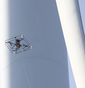 A quadcopter captures images of a wind turbine blade that are then added to an asset management map.