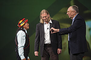 Domingo Ankuash, a leader of the Shuar nation in Ecuador, presents a ceremonial spear to Esri president Jack Dangermond at the 2016 Esri User Conference in San Diego. The spear signifies friendship between the indigenous nations of Ecuador and the GIS community. Richard Resl of AmazonGISnet watches Dangermond receive the spear.