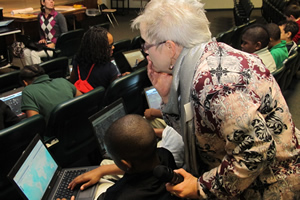 Beverly Richey helps a sixth grader at Ed White Middle School work with an online map.