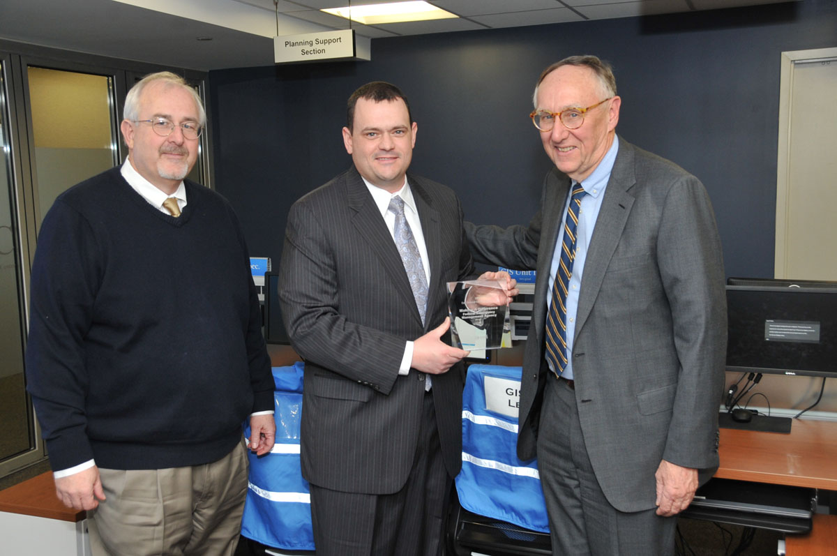 Jack Dangermond, Esri president, presents the 2013 Making a Difference Award to Christopher Vaughan, FEMA geospatial information officer, and FEMA administrator Craig Fugate.